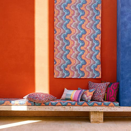 orange wall, ethnic bench and tapestry by Interior Design Studio Costa Blanca Second Home
