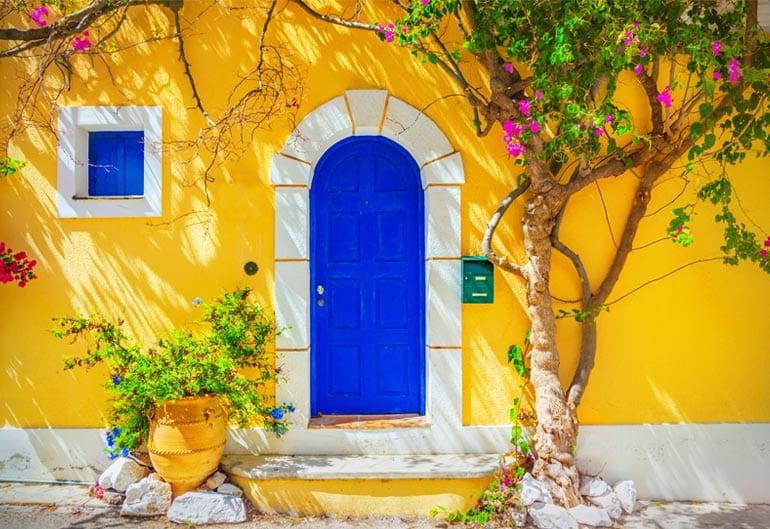 Ibiza Interior Design of yellow mediterranean house with blue door and window