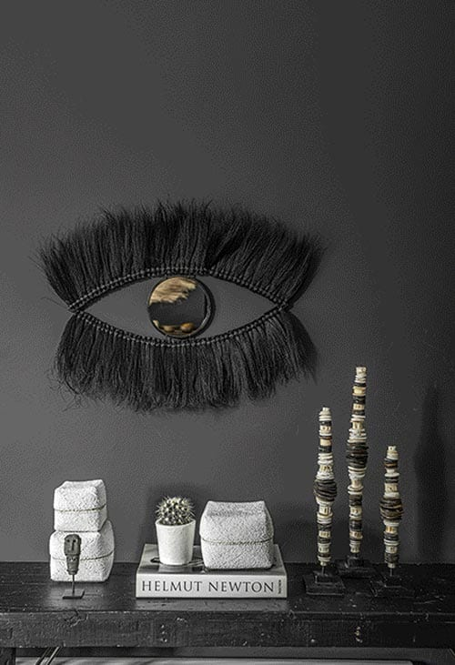 Art piece black eye, white books, candles on marble bookshelf by Costa Blanca luxury interior designer