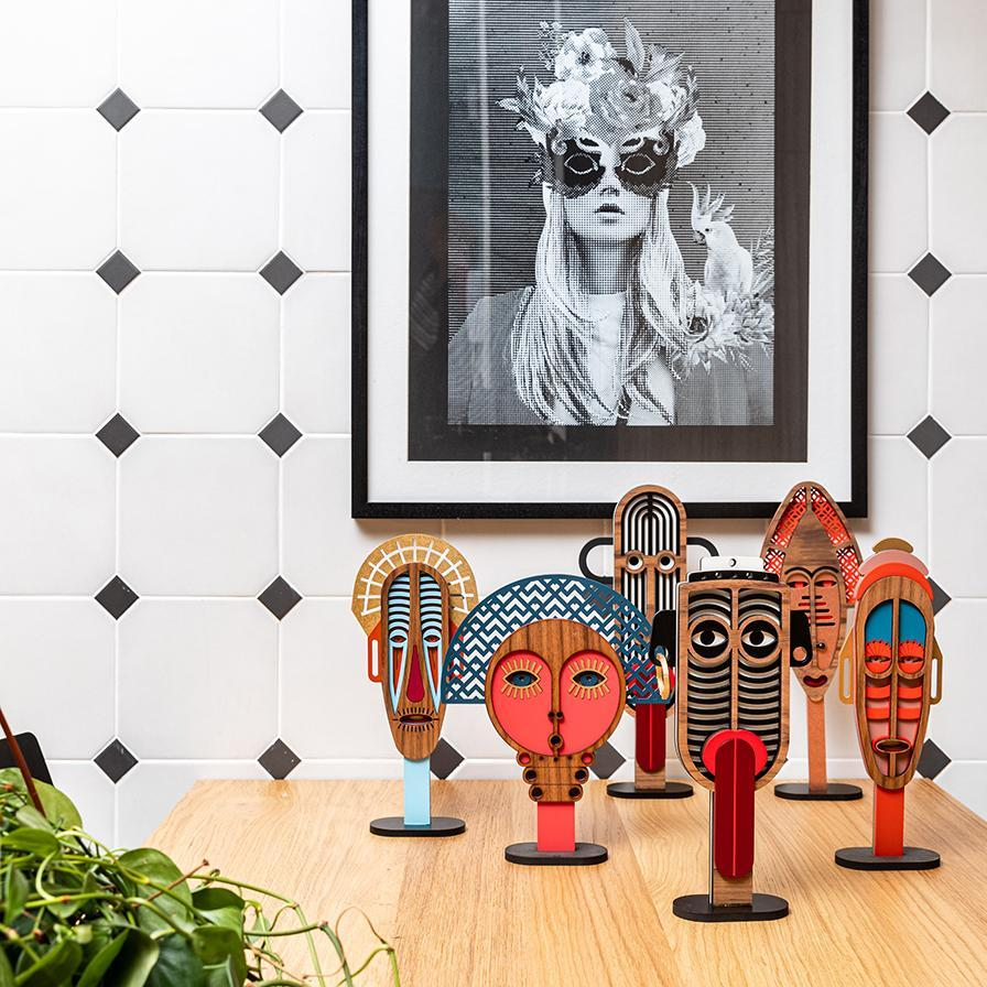 home interior styling checkered wall with picture of masked woman and masks on table