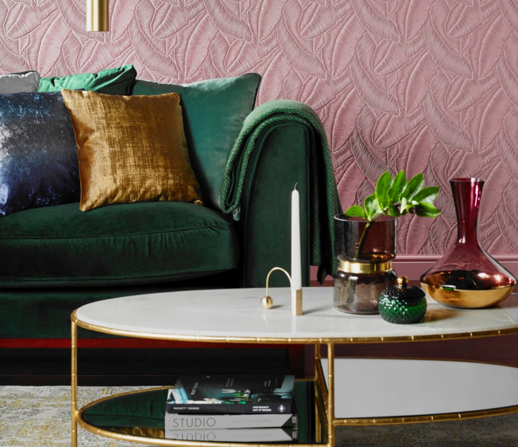 home interior styling pink wall behind green sofa and white coffee table